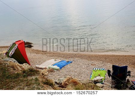 Beach gear towels mats chair tent and clothes on empty pebble shore on summer day on blue sea