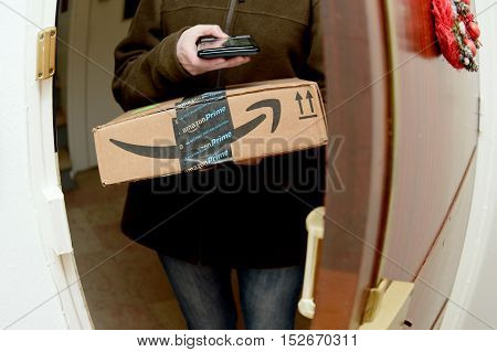 PARIS FRANCE - JAN 27 2016: Ultra wide lens - Woman scanning on device to delivery parcel from Amazon.com online shopping