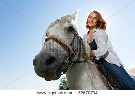 Close-up portrait of happy young woman riding white horse, against blue sky