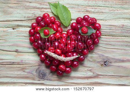 fresh seasonal red cherry berry fruit with healthy vitamins on wooden or wood table laying in shape of heart as love symbol of valentines day holiday and smiley face with green leaves and spikelet