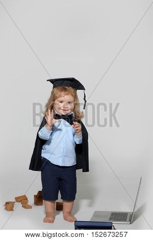 Small boy child with long blond hair in blue shirt black graduation gown and cap playing with wooden blocks near notebook and diaries isolated on white background