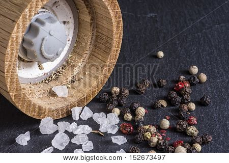 Pepper Mill, Sea Salt And Pepper Grains On Dark Stone Surface Close Up
