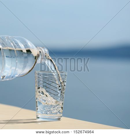 pure drinking water from plastic bottle pouring into glass outdoor on summer day on blue sea