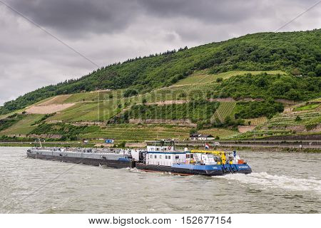 Trechtingshausen Germany - May 23 2016: Tanker barge (tank/gas) Thera on the Rhine River near Trechtingshausen in cloudy weather Rhine Valley UNESCO World Heritage Site Rhineland-Palatinate Germany.