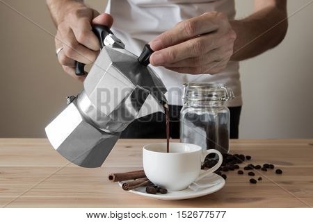 Pouring coffee out of italian coffee pot. Male hands pouring coffee out of italian coffee pot in front of minimalistic background with coffee beans and cinnamon