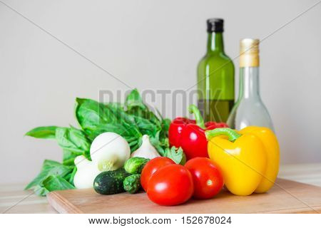 Vegetables ingredients on kitchen table. Fresh vegetables, basil, olive oil and vinegar on wood kitchen table in front of white wall.