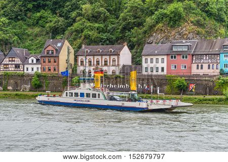 Niederheimbach Germany - May 23 2016: Ferry on the Rhine River near Niederheimbach in cloudy weather Rhine Valley UNESCO World Heritage Site Germany.