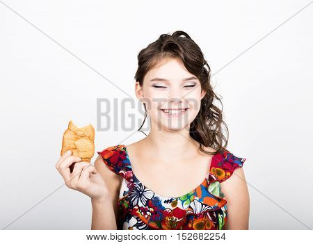 Young smile girl holding and biting bread roll.