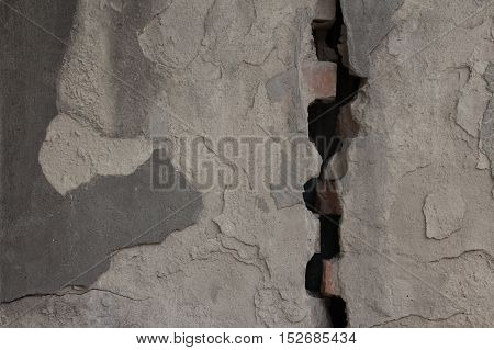 Gray flaked plastered wall divided by wide crack. Rough uneven texture