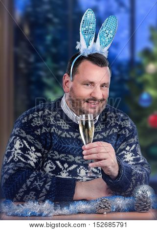Mature dude in blue bunny ears sits at the desk with glass of white dry wine. Bearded man in Scandinavian sweater is toasting a Merry Christmas