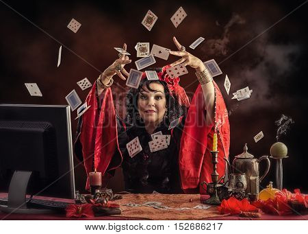 Mature Gypsy female soothsayer tossing playing cards up to predict future her online client. Black-haired diviner wears red-black blouse sitting at the desk with smoking candles and other occult items