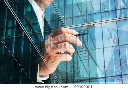 Double exposure of young businessman and town bridge drafting construction plan with ballpoint. Conceptual shoot of modern architectural design of big city.