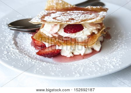 Millefeuille with strawberries and powdered sugar sprinkled on plate poster