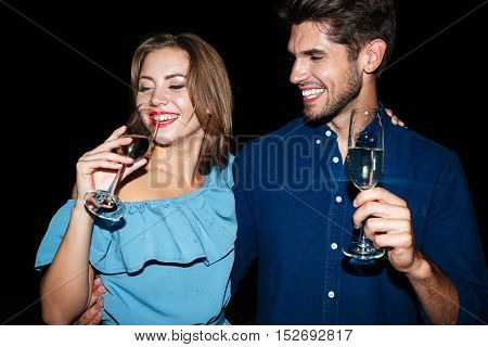Smiling beautiful young couple standing and drinking champagne at night together