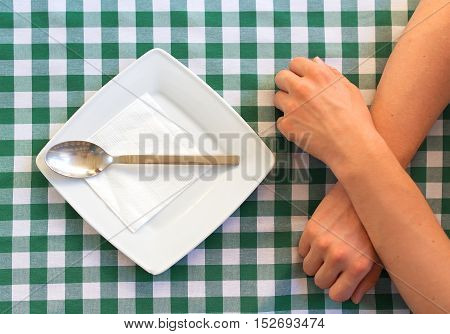 Empty Square Plate With Silver Spoon, Crossed Human Hands.