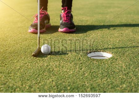 Golf player at the putting green putting golf ball into a hole. Golf sport concept.