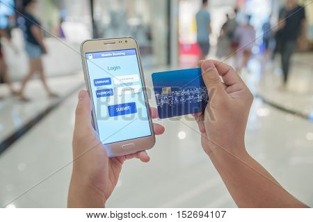 Woman verified account balance on smartphone with mobile banking application and credit card. Online shopping.