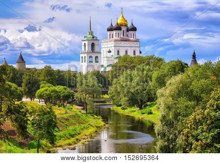 The golden dome of Trinity Church and towers of Pskov Kremlin (Krom) reflecting in the river Pskov Russia. poster