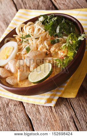 Malaysian Laksa Soup With Chicken, Egg, Noodles And Herbs Close Up In A Bowl. Vertical
