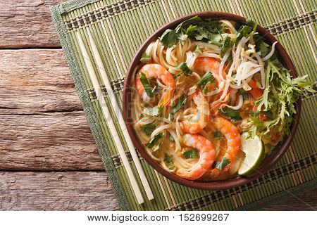 Malaysian Laksa Soup With Shrimps, Noodles And Herbs Close Up In A Bowl. Horizontal Top View