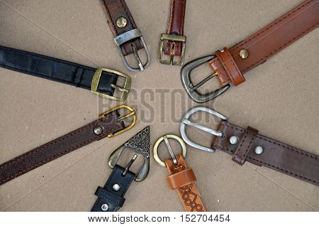 Fashion background. Vintage brown leather belts with metal rusty buckle on beige cardboard surface arranged in a circle closeup.