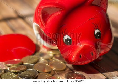 A broken piggy bank with many coins