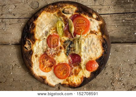 Burnt pizza with tomatoes, salami,pepperoni Overhead view
