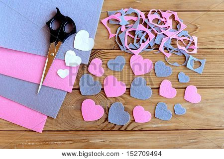 Hearts cut from felt, felt sheets set, felt scraps, paper patterns, scissors on wooden background. How to cut different hearts from felt. Children development of fine motor skills