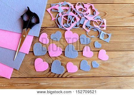 Hearts cut from felt, felt sheets set, felt scraps, scissors on wooden background. Learn to cut shapes from the felt. Development of fine motor skills in children