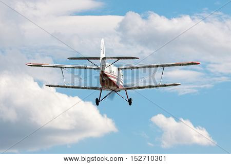 Kiev Region Ukraine - September 28 2010: Antonov An-3 biplane landing with cloudy sky on the background - rear view