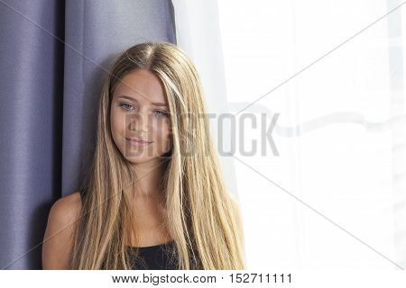 Portrait of beautiful girl blonde european model with blue eyes looking down in front of the camera with window behid tranquil an calm pose space for copy text