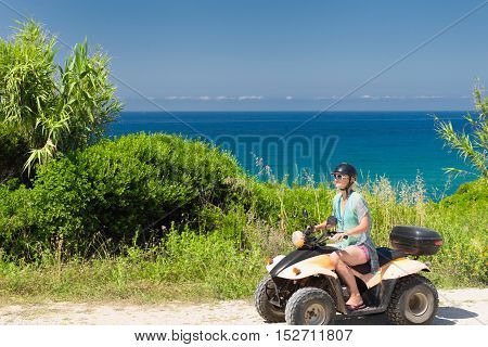 Young woman driving quadbike by the sea