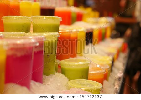 Variety of colorful, fruity drinks on ice in a Barcelona, Spain market