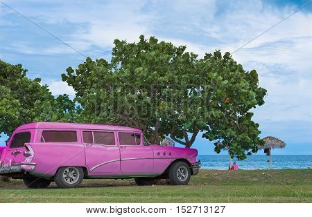 Santa Clara, Cuba - September 09, 2016: American rose Buick classic car parked on the beach in Santa Clara Cuba - Serie Cuba 2016 Reportage