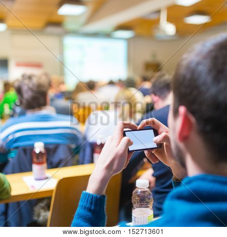 Workshop at university. Rear view of participant listening to lecture and making notes on smarth phone. Using online tools and aplications in education and everyday life.
