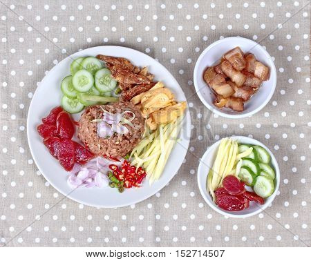 Thai food ,Fried jasmine rice with shrimp paste,(Kao Klok Kapi in Thai) served with green sour mango roll,Chinese sausage,crispy dried fish,shrimp,minced chili,shallots,stir sweet pork ,sliced cucumber and scrambled egg . poster