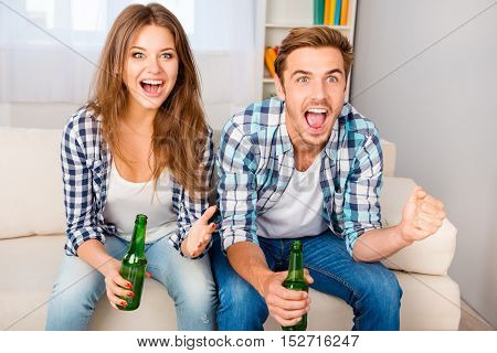 Young Happy Excited Man And Woman Watching Football With Beer