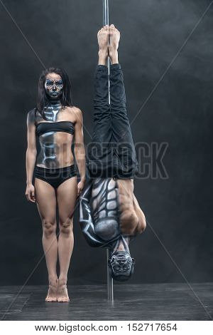 Unbelievable couple of pole dancers with a horrific body-art in the dark studio with a cloud of a smoke. Man hangs upside down on a pylon. Girl stands on her toes next to him. Vertical.