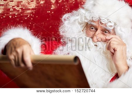 Checking his special list. Traditional Santa Claus sitting at his chair and reading a letter