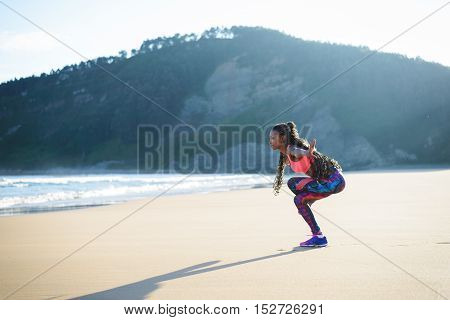Black fitness woman practicing balance yoga exercise towards the sea during outdoor workout at the beach. Dancing equilibrium training.