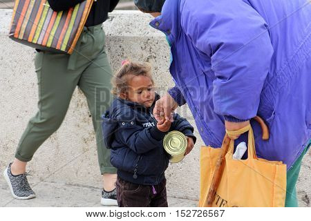 SKOPJE MACEDONIA - OCTOBER 18  2016:Older woman gives money to cute beggar girl downtown of Skopjecapital of Macedonia