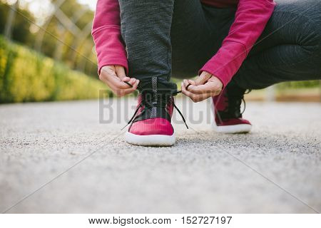 Sport and outdoor fitness workout concept. Woman lacing sneakers before training. Sport footwear close up.