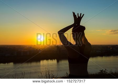 Two shots - sporty woman in lotus position in the park at sunset. Lotus mudra. Sunset light, golden hour, lens flares. Freedom, health and yoga concept