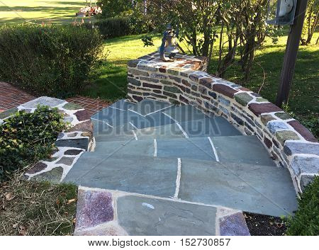 flagstone pavers for curved steps leading down to a brick pathway in a garden