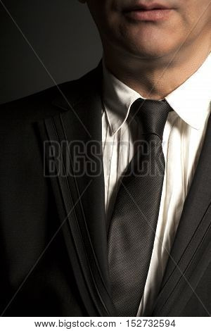 Man in black suit and black tie on a black background