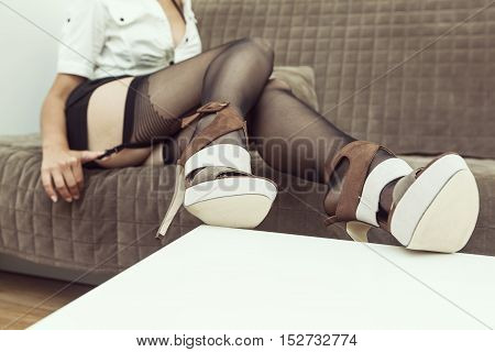 Girl lying on couch showing her legs sexy stockings with high heels one hand holding garter in sexy pose feet up on white small table no head visible space for copy text at the bottom selected focus on legs and shoes