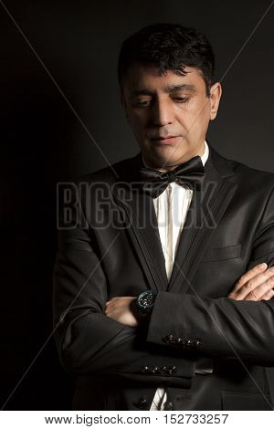 Elegant man wearing black bow tie and black suit on black background