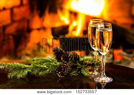 Two glasses of sparkling white wine and New Year Christmas decoration in front of warm fireplace. Romantic, cozy relaxed magical atmosphere near fire. New Year or Christmas concept