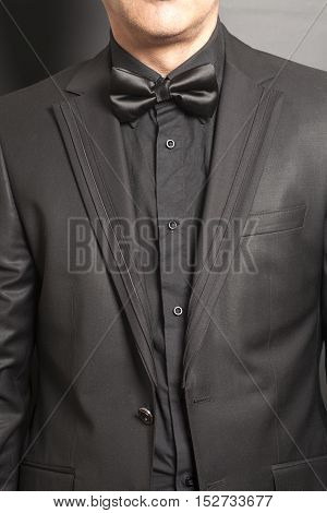 man wearing a black suit and bow tie on gray background