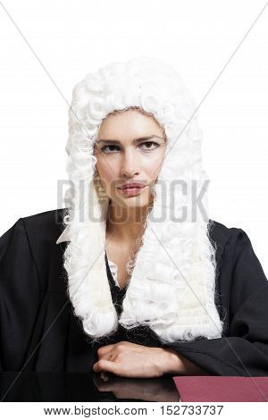 Female judge wearing a wig and black mantle isolated on white backgriund